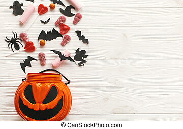 Halloween Jack o Lantern bucket with holiday candy, bats, spiders, skulls on white rustic wood, flat lay. Space for text. Halloween background. Season's greeting card mockup