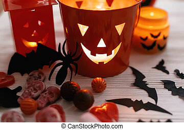 Halloween Jack o Lantern, bucket with holiday candy, bats, spiders, skulls on white rustic wooden background. Trick or treat. Halloween background. Season's greeting card