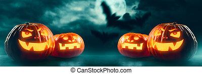 Halloween Jack O' Lantern pumpkins on dark night background