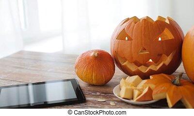 halloween jack-o-lantern, pumpkins with tablet pc -...