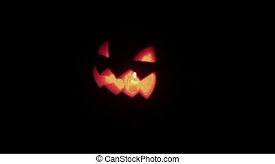 Halloween Jack o lantern with burning candle floats in dark space