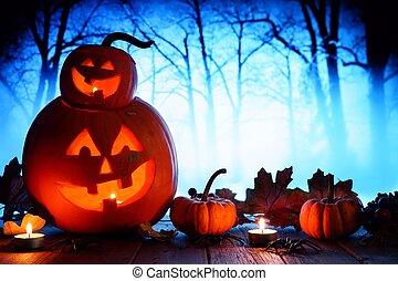 Halloween Jack o Lanterns against spooky blue lit forest