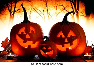 Halloween Jack o Lanterns against spooky orange lit forest -...