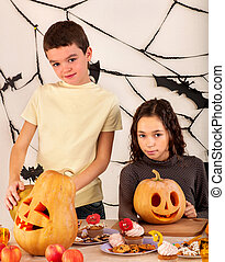 Halloween kids holding carved pumpkin .