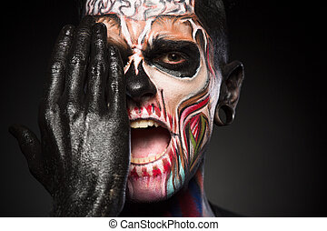 Halloween makeup concept, man covering zombie face with black painted hand.