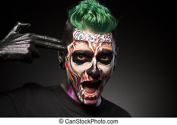 Halloween makeup, man with skeleton colored face touching temple.