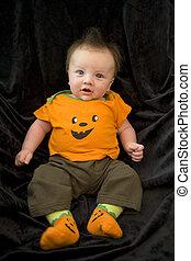 A baby boy in a Halloween outfit.