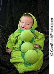 A baby boy in a pea pod Halloween outfit.