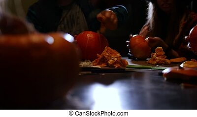 Halloween party. A group of people cutting the pumpkin