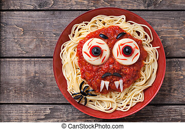 Halloween party creative decoration food. Spaghetti monster face with big eyeballs, fangs, spider and moustaches in red dish on vintage wooden table background.