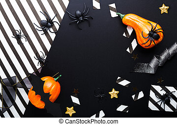 Halloween party invitation mockup, celebration. Frame. Halloween decorations concept with bats, spiders, jack-o'-lantern, stars, confetti, ribbon. Flat lay, top view, copy space on black and white background.