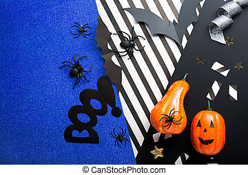 Halloween party invitation mockup, celebration. Halloween decorations concept with bats, spiders, jack-o'-lantern, stars, confetti, ribbon. Flat lay, top view, copy space on black, white and blue background.