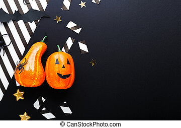 Halloween party invitation mockup, celebration. Halloween decorations concept with bats, spiders, jack-o'-lantern, stars, confetti, ribbon. Flat lay, top view, copy space on black and white background.