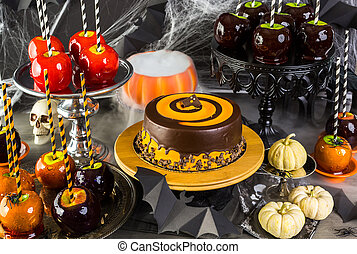 Halloween - Table with colored candy apples and cake for...