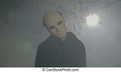 Halloween portrait of a frightening zombie covering his face with a mask inclining his head while looking at the camera