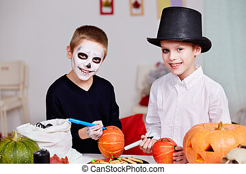 Halloween preparations - Photo of two eerie boys drawing on...