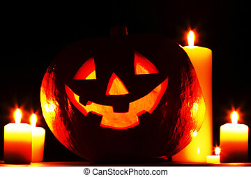 funny halloween pumpkin and burning candles on black background