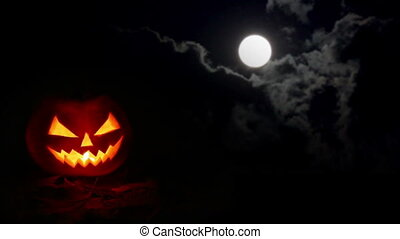 Halloween pumpkin at night and moon in clouds