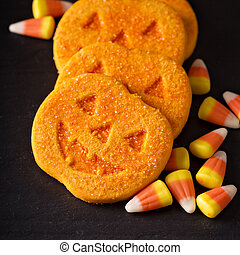 Halloween pumpkin cookies and candy on black background