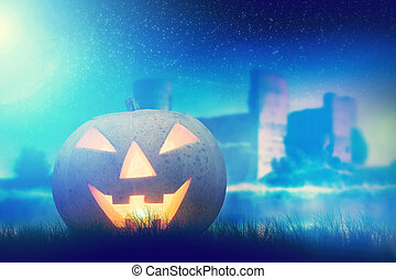 Halloween pumpkin glowing in dark, misty scenery with gothic castle and moon