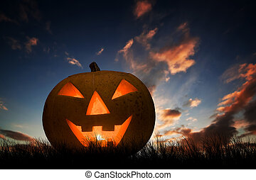 Halloween pumpkin glowing under dark sunset, night sky. Jack o'lantern