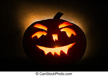 Halloween pumpkin head jack lantern with burning candles on orange background