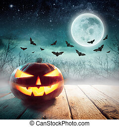Halloween Pumpkin in a dark mist Forest. Elements of this image furnished by NASA