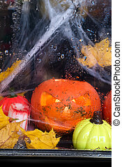 Halloween pumpkin in the mystical house window with rain drope and spider web