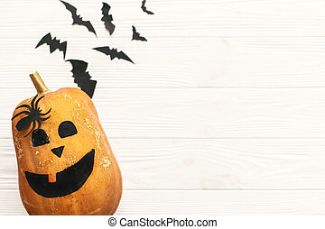 Halloween pumpkin Jack o Lantern flat lay with bats, spiders top view on white rustic wooden background. Trick or treat. Space for text. Season's greeting card mockup.