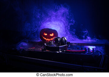 Halloween pumpkin on a dj table with headphones on dark background with copy space. Happy Halloween festival decorations and music concept