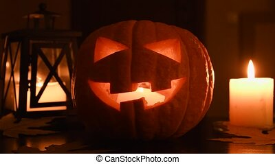 Hand lits Halloween pumpkin with match. Glowing Jack o'Lantern on table at home. Candle and lantern on background. All Saints day.