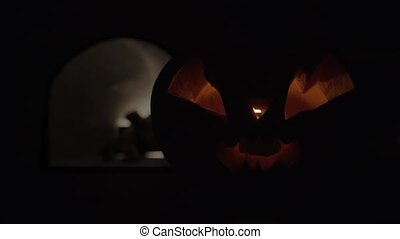 Halloween pumpkin with a sinister face with a flickering ...