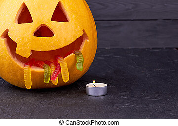 Halloween pumpkin with candle on dark background.