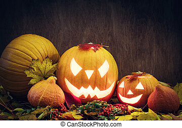 Halloween pumpkins glow, carved jack-o-lantern in fall leaves