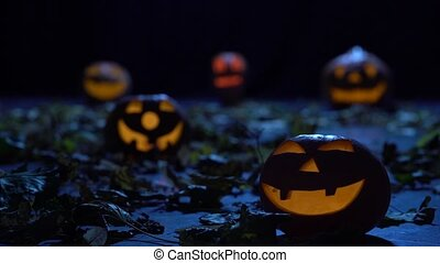 Halloween pumpkins glow in the forest with horrible faces,...
