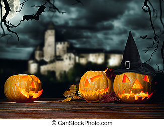 Halloween pumpkins on wood with dark background - Concept of...