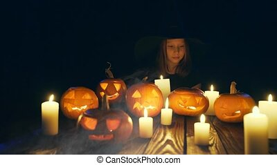 Halloween pumpkins on wooden planks - Girl in costume of...