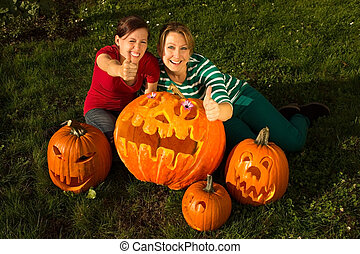Halloween pumpkins - Two girlfriends with their carved...
