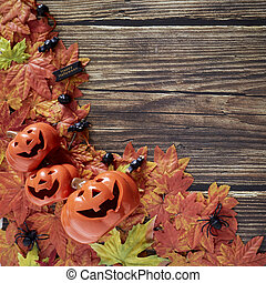 Halloween pumpkins with autumn fall leaves over wooden