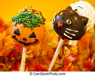 Halloween gourmet cake pops with holiday decor on orange backround.