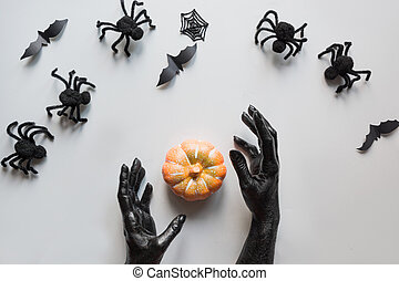 Halloween spider, pumpkin, bat, female hands covered black paint on grey. Flat lay, top view. Creative Halloween Day composition.