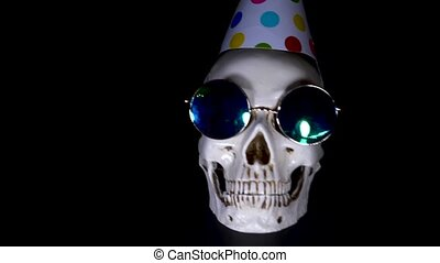 Halloween. the skull in a festive cap on a black background....