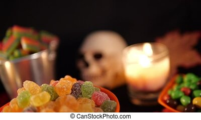 Halloween theme candy with burning candles over black background footage