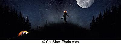 Halloween theme: scary maniac with pumpkin head in dark forest