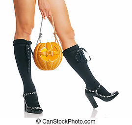 Halloween witch holding carved pumpkin near her legs.