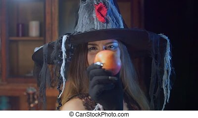 Halloween witch in a hat is holding a poisonous apple....