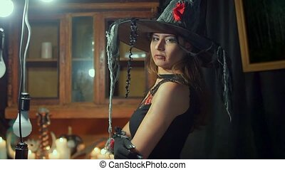 Halloween witch in a hat is looking into the camera. She...