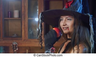 Halloween witch in a hat with a poisonous apple looks...