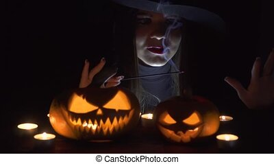 Halloween Witch with a magic Pumpkin. Beautiful young woman in witches hat and costume holding carved pumpkin. Halloween art design.