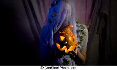Halloween Witch with a magic Pumpkin in a dark room. Beautiful young woman in witches hat and costume holding carved pumpkin.